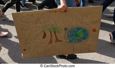 Marching with a crowd of demonstrators at a peaceful environmental protest. One activist is carrying a placard that says save the planet in french