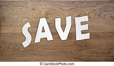 SAVE word cut from white paper put on old wood table. Saving money business concept