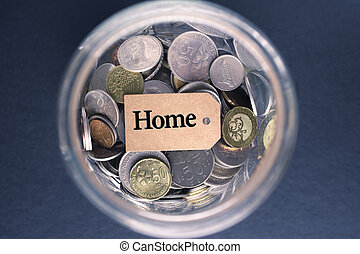 Saving Concept : Home label with coins in the glass