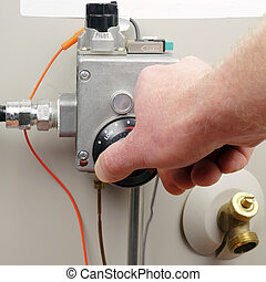 Saving Energy - Hand of a man turning down household gas...