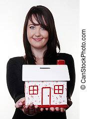saving for a house - woman holding out a money box in the...