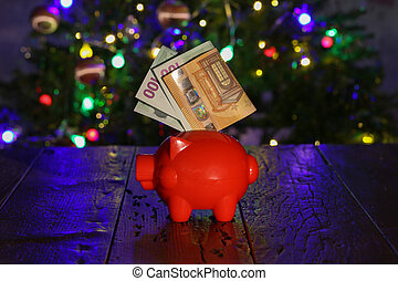 Saving for Christmas gifts. Piggy bank with euro notes