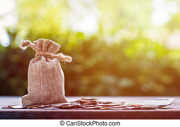 Saving money for future, home, car, education, investment, descendants concept : Money bag with many coins on wood table with green nature as background. Copy space for your text.
