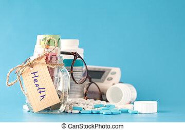 Saving money for health care insurance - money glass, pills and bottles