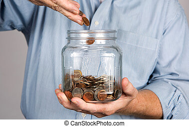 Saving Money In Jar - Man drops money into a glass jar for a...
