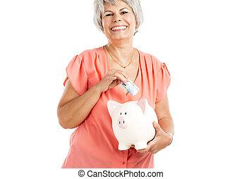 Saving money - Portrait of a happy old woman putting money...