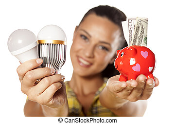 saving money with LED - Smiling girl shows that you can save...