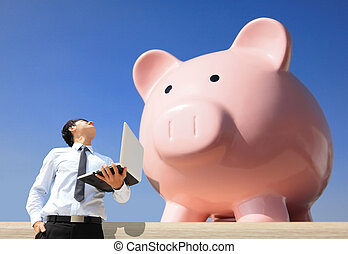 Saving Money with my piggy bank - Young business man look to piggy bank with computer