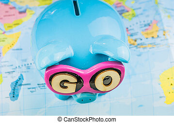 Saving piggy bank from TOP view. GO slogan on sunglasses . Pig is staying on the world map ready for travel.