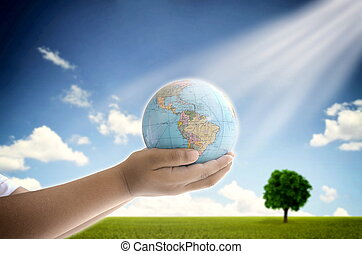 Saving the planet - A conceptual image of a boy holding the...
