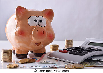 Savings and accounting with piggy bank money and calculator front