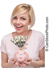 Savings. Attractive young blond hair woman holding a piggy bank with dollars in it and smiling while isolated on white