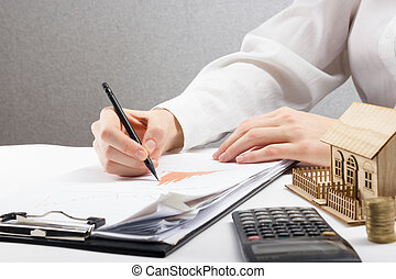 Savings, finances, economy and home budget concept - close up of woman counting at calculator  losses, profit  making notes, working with statistics, analyzing financial results
