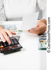 savings, finances, economy and home concept - close up of hands with calculator counting money and making notes at home