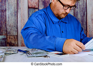 savings, finances, economy and home concept close up of man with calculator counting money and making notes at home