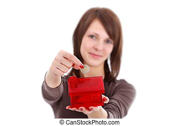 Savings for a new home - Woman putting coins in money box...