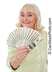 Savings. Happy senior woman stretching out hand with paper currency while standing isolated on white background