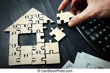 Savings on the purchase of real estate or a mortgage. A hand is collect a house from pieces of a puzzle.