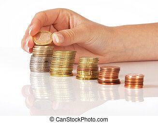Savings - Female hand putting coins on little stacks