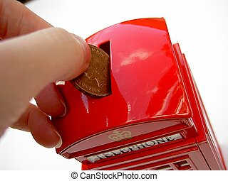 Savings - Putting money in savings box shaped like a...