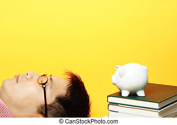 Savings - A man lying next to a piggy bank on top of stack...