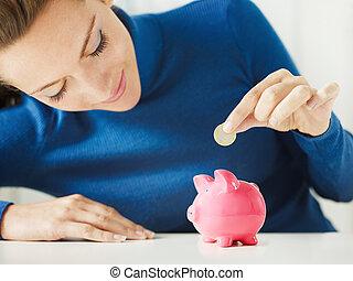 Savings - woman putting 1 euro in small piggy bank. ...