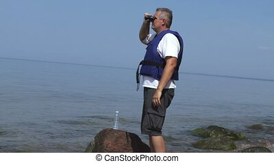 Savior at the sea looks the binoculars