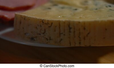 Savory and fresh cheese and pork ham ready to be cut as appetizer, 4K video. Slowmotion
