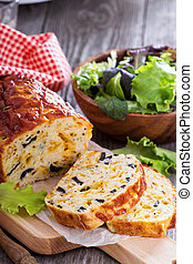 Savory cheese loaf with olives on cutting board