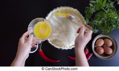 Woman hands press the edges of a savory pie with their fingers to close them, then brush the surface with egg yolk.