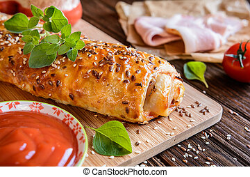 Savory strudel with ham, cheese, tomato sauce and herbs