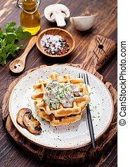 Savory waffles with corn and mushroom creamy sauce on a wooden background Top view