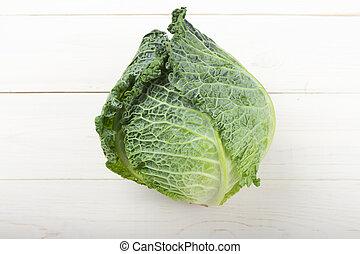Savoy cabbage on a white wooden background.