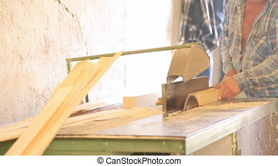 Sawing the wooden square beam on circular saw