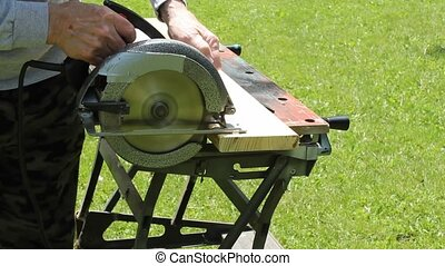 sawing wood - trimming a board to length with an electric...