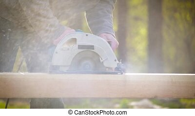 Sawing wooden beam lengthways with a circular hand saw...
