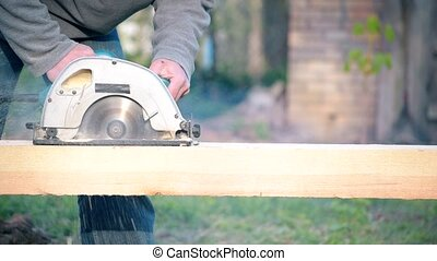 Sawing wooden beam with circular hand saw - Sawing wooden...
