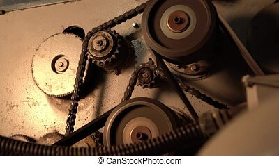 Close-up view of gears and chain rotate on machine