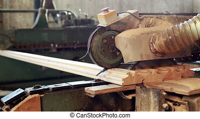 Sawmill. View of saw cuts off excess profiled bar, close-up