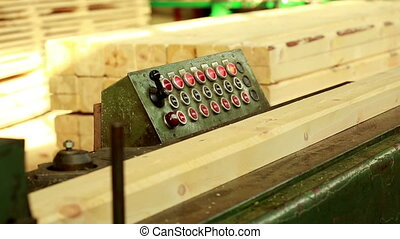 Sawmill. View of wooden bar moves on conveyor, close-up