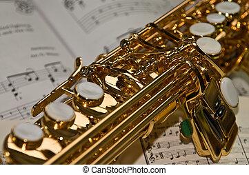 Sax body - Golden soprano saxophone lying on sheet music