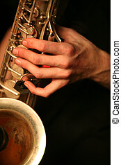 Saxophone - Hands of the saxophonist with a saxophone on a...