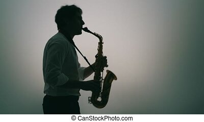 Saxophone player over a light grey background.