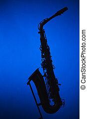 Saxophone Silhouette Against Blue Soptlight - An alto...