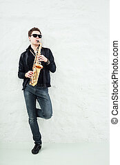 Saxophone - Young man playing sax laening against a wall