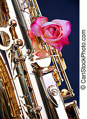 A pink rose mounted on a gold brass saxophone isolated against a dark blue background.