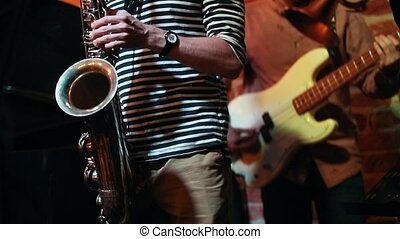 Saxophonist and guitarist masterly play at a performance in...