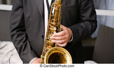 Saxophonist in a black suit playing on golden saxophone. Jazz music.