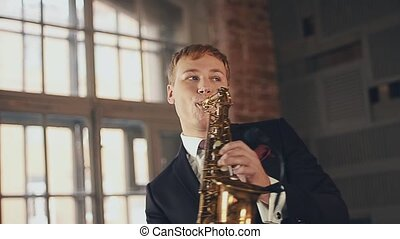 Saxophonist in black suit play jazz on golden saxophone. Musician. Performing