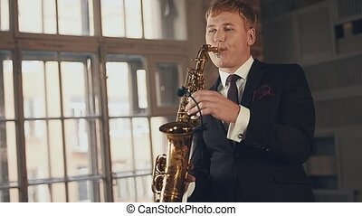 Saxophonist in black suit play jazz on golden saxophone. Vocalist on stage